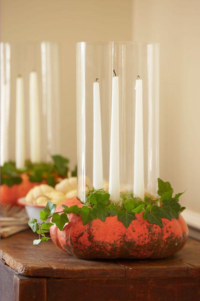 viele lange weiße kerzen und ein kleiner kranz aus kleinen grünen blättern, ein tisch aus holz und ein kleiner oranger halloween kürbis