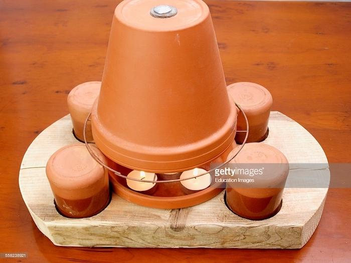 ein tisch aus holz und ein holzbrett, bastelideen für erwachsene, ein teelichtofen aus einem braunen blumentopf aus keramik und mit kleinen weißen teelichtern