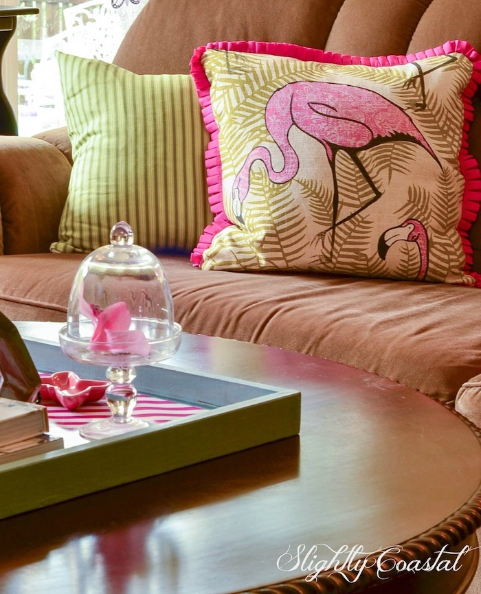 wohnzimmer einrichtung ideen, flamingo deko, ein braunes sofa mit einem pinken kissen mit einer pinken flamingo mit pinken federn und grünen blättern