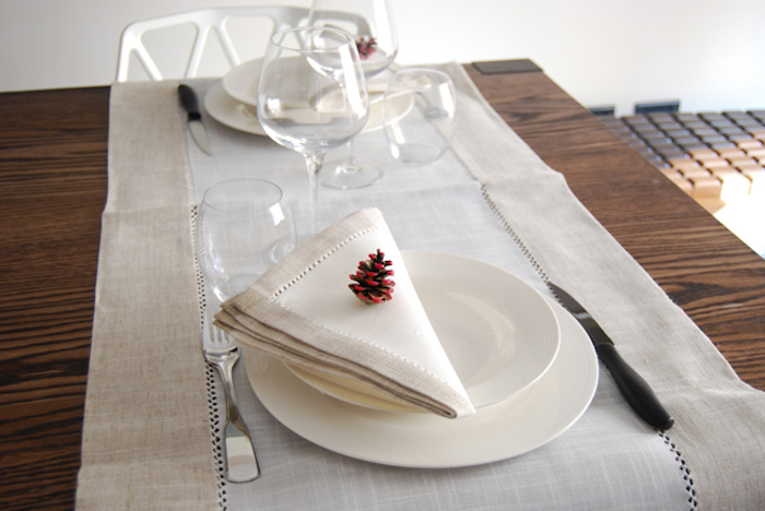 ein brauner tisch aus holz und mit einer tannenzapfen deko, tisch mit einer weißen decke und mit weißen tellern und gläser, messer und gabel, ein kleiner bemalter roter tannenzapfen