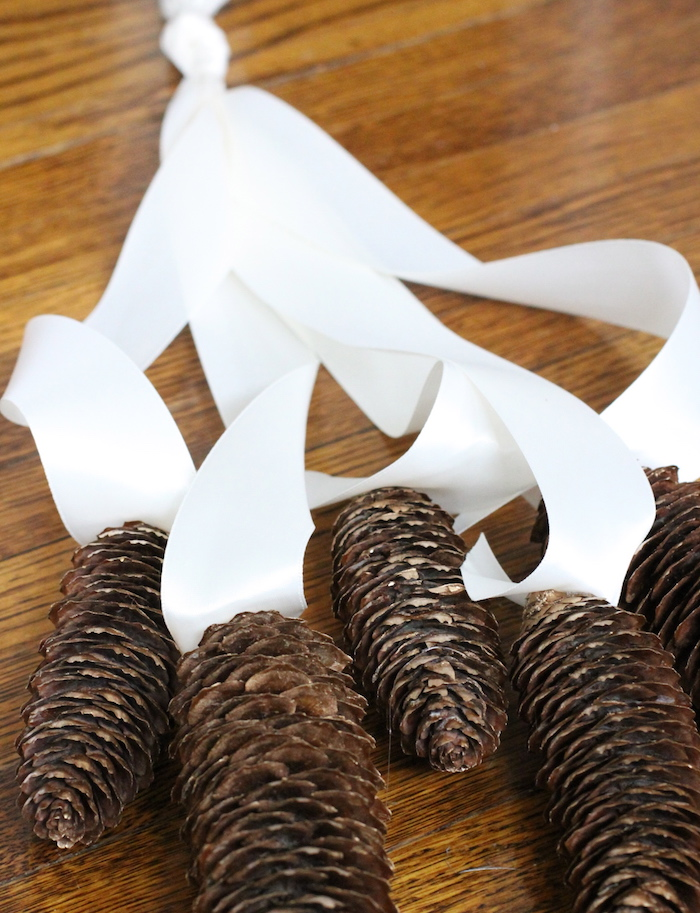eine tannenzapfen deko mit einer langen weißen schleife und mit vielen großen braunen tannenzapfen, ein brauner tsch aus holz, große tannenzapfen basteln