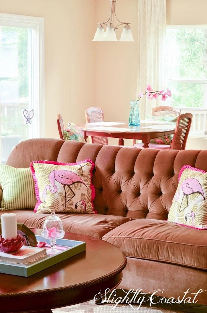eon wohnzimmer mit einem braunen sofa mit kleinen kissen mit pinken flamingos und ein tisch aus holz und eine blaue vase, wohnzimmer deko ideen