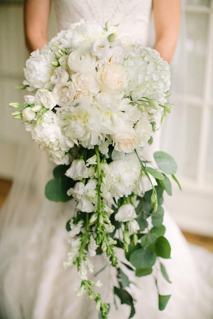 eine junge braut mit einem großen weißen brautstrauß wasserfall mit vielen weißen rosen und grünen langen blättern, eine braut mit einem weißen brautkleid, brautstrauß vintage