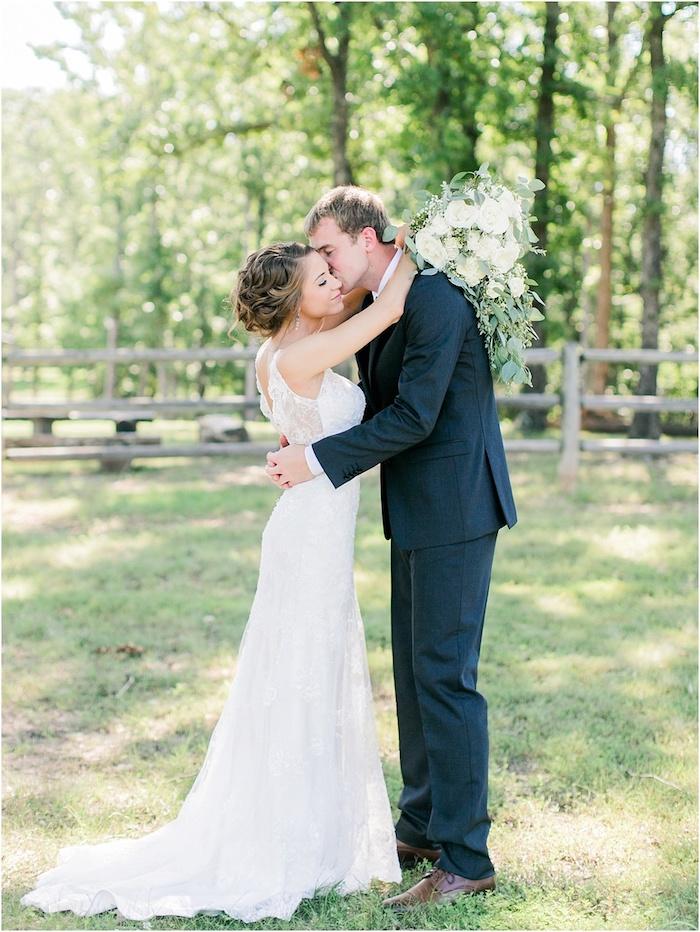 ein mann und eine junge braut mit einem weißen brautkleid und mit einem grpben weißen brautstrauß wasserfall mit weißen rosen und grünen blättern