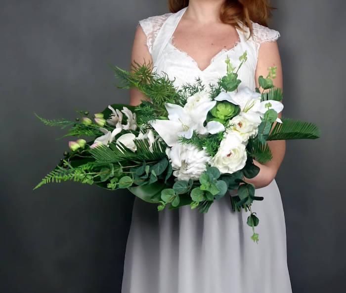 eine schwarze wand und ein brautstrau hortensie und eine junge braut mit einem weißen brautkled und einem v mit vie3len weißen rosen und grünen blättern