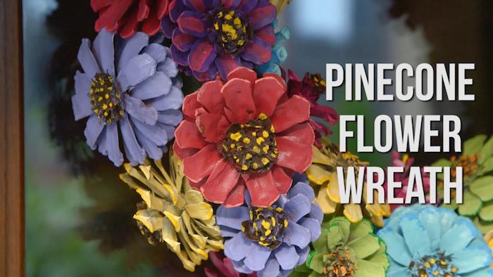 ein kranz mit vielen violetten, gelben, grünen und roten blumen aus vielen bemalten kleinen tannenzapfen, basteln mit tannenzapfen, kleine tannenzapfen bemalen