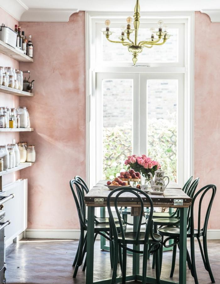 Esszimmer in altrosa Farbe von nah, grüne Stühle, Süßigkeiten zum Naschen, ein Kronleuchter