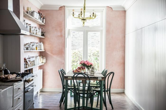 ein Esszimmer mit Altrosa Wandfarbe, sieben Stühle, ein großes Fenster, Regale,