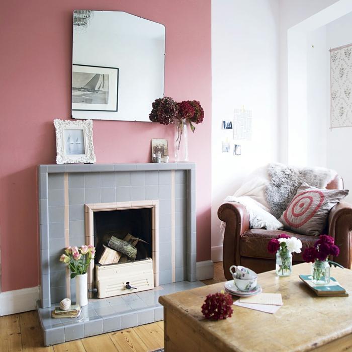 Altrosa Wandfarbe, ein grauer Kamin, ein schöner Spiegel, ein Ledersessel mit Kissen