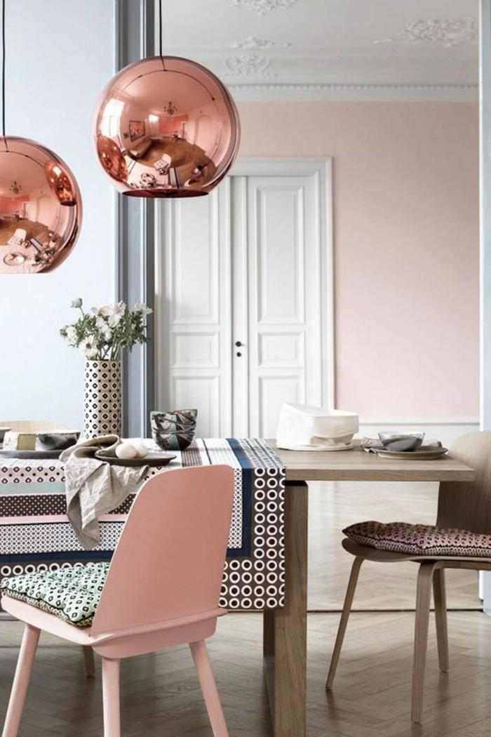 altrosa Wandfarbe, ein kleiner Tisch mit bunter Decke, zwei hängende runde Lampenschirme