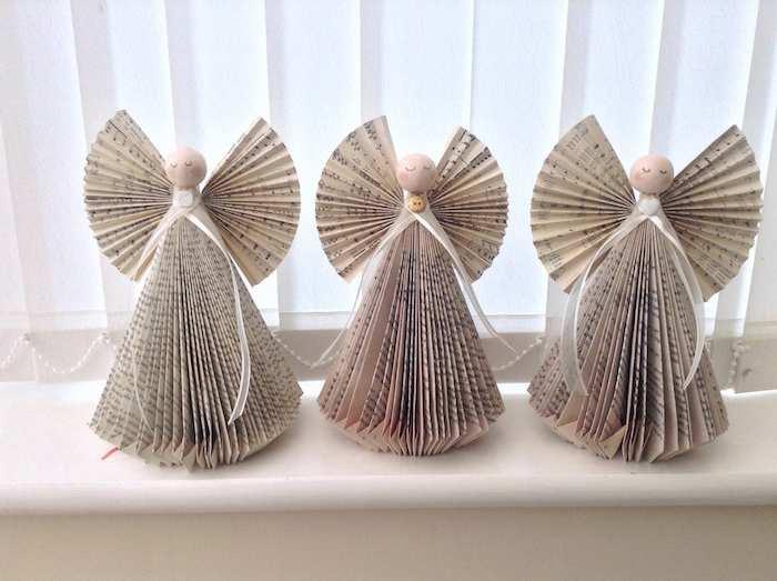 drei kleine weiße engel mit schleifen und flügeln und aus vielen gefalteten weißen seiten mit schwarzen buchstaben, ein fensterl engel basteln aus papier