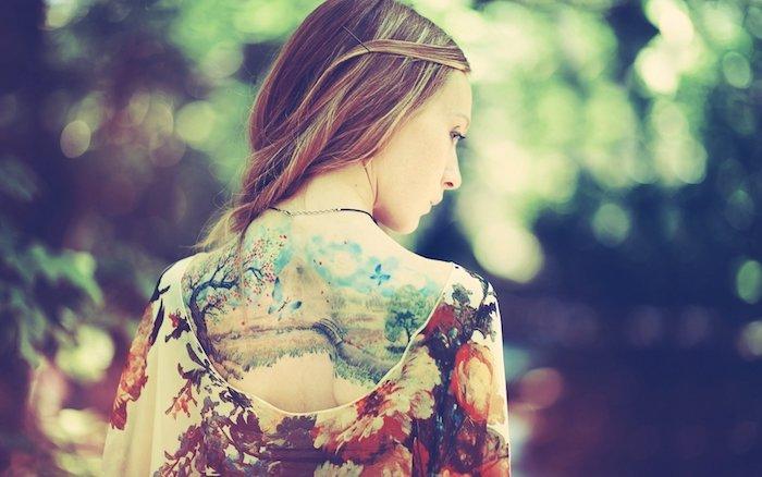 eine junge frau im außenbereich und mit einer kette und ein tattoo rücken frau mit vielen blauen schmetterlingen und schwarzen bäumen