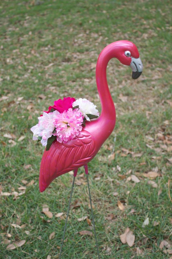 ein rasen und ein garten mit einer dekorativen violetten flamingo mit großen weißen, pinken und violetten blumen