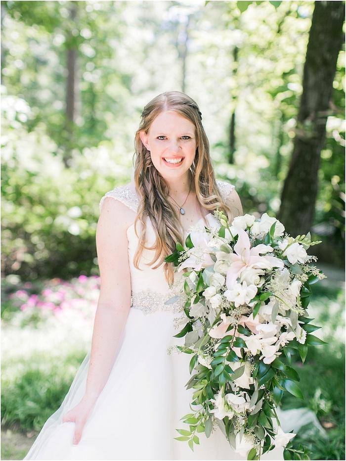 ein garten mit vielen grünen bäumen und eine junge braut mit einem weißen kleid, ein großer weißer brautstrauß mit vielen weißen blumen und mit grünen langen blättern