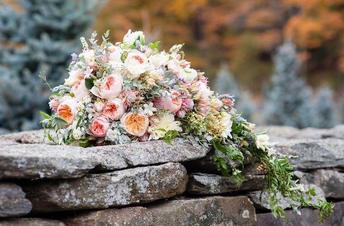 eine wand aus grauen steinen in einem garten und ein großer brautstrauß wasserfall mit vielen pinken und gelben und orangen rosen und grünen blättern, ein brautstrauß vintage