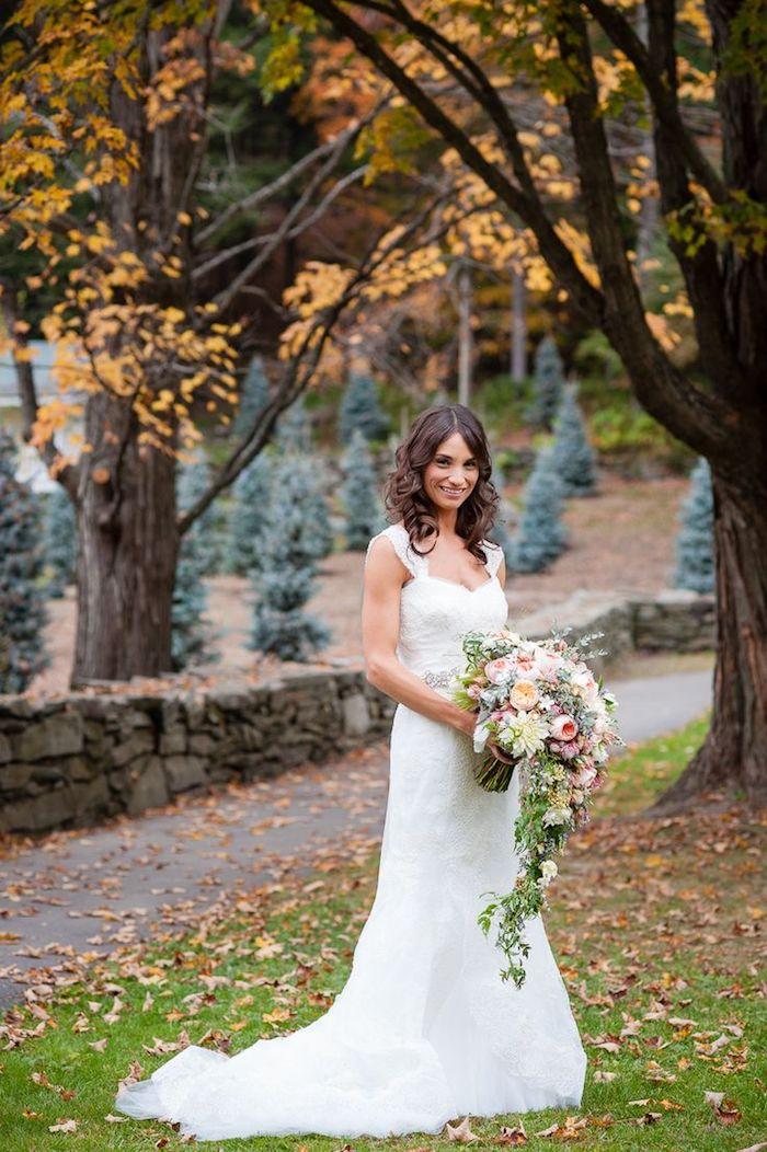 ein brautstrauß vintage mit vielen pinken, gelben und orangen rosen ud vielen grünen blätern, eine braut mit einem weißen brautkleid im garten