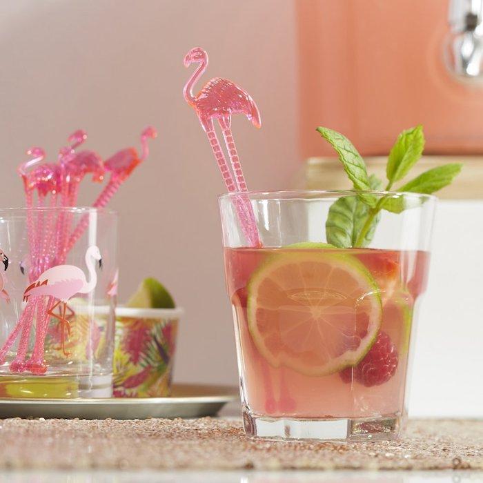 ein glas mit einem pinken cocktail mit einer grünen zitrone und mit pinken flamingo cocktail stäbchen