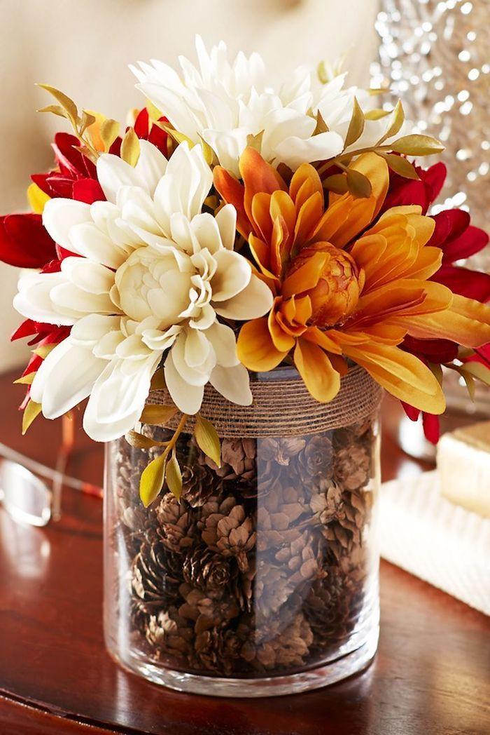 ein tisch aus holz und ein glas mit vielen kleinen braunen tannenzapfen und mit großen weißen, roten und orangen blumen, tannenzapfen deko