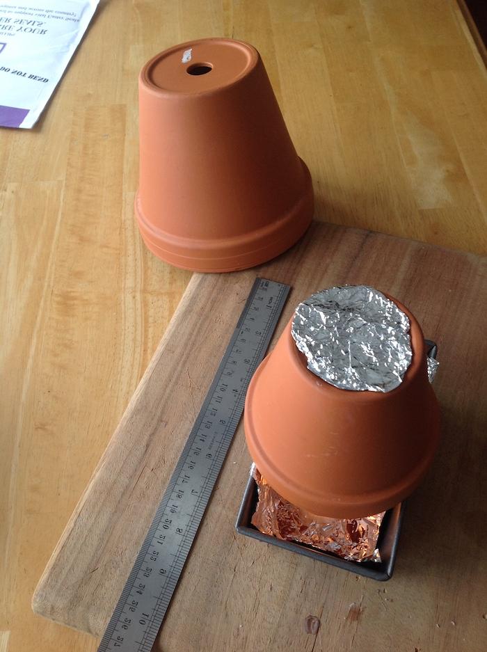 ein langes graues lineal und ein holzbrett, einen teelichtofen selber bauen aus zwei kleinen braunen blumentöpfen aus keramik, ein tisch aus holz