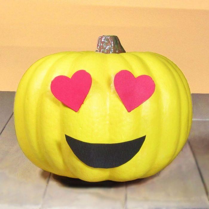 ein tisch aus holz und ein großer gelber kürbis mit zwei roten großen augen aus herzen aus papier, halloween deko basteln, kürbisgesichter vorlage