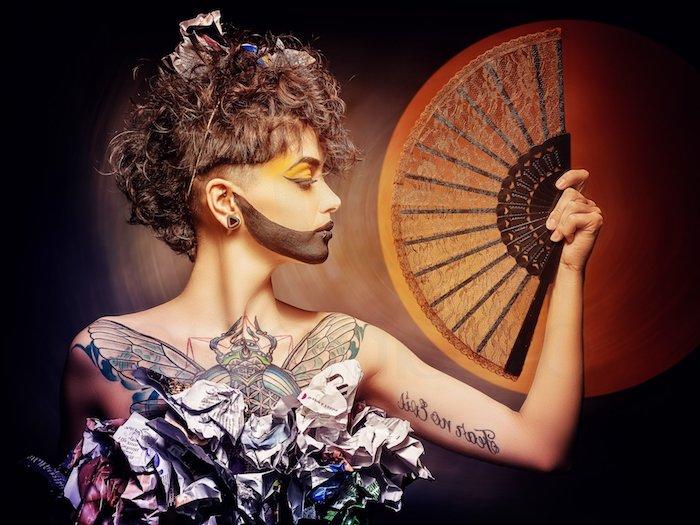 eine junge frau mit einem großen orangen fächer und mit einer hand mit einem schwarzen schriftarten tattoo, ein tattoo brust frau mit einem insekten