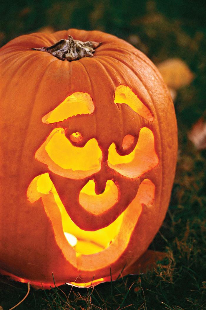 ein großer oranger kürbis mit einem gruseligen kürbisgesicht mit einer gelben nase und mit gelben augen, kürbisgesichter schnitzen, einen halloween kürbis schnitzen