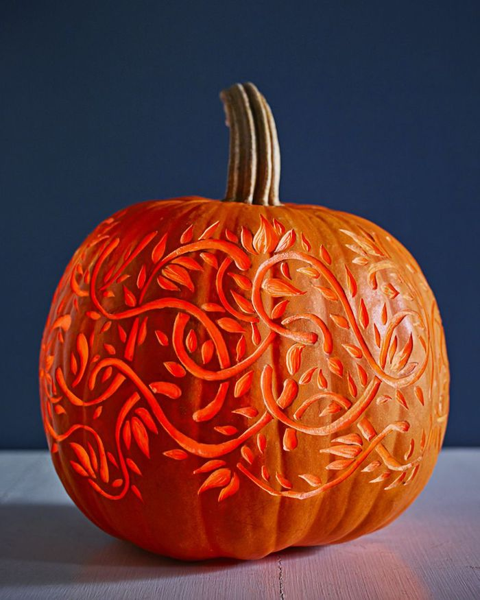 eine blaue wand und ein kleiner oranger kürbis mit pflanzen mit orangen blättern, kürbis halloween schnitzen ideen