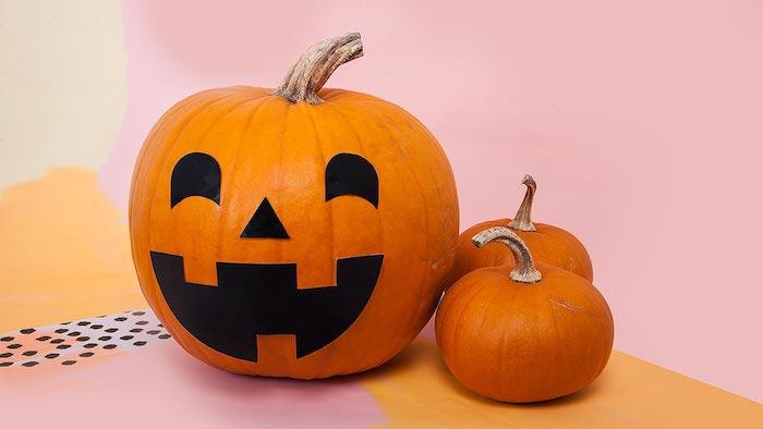 violette und orange wände und drei kleine und große orange halloween kürbisse, ein kürbis gesicht aus papier und mit schwarzen augen, halloween deko basteln
