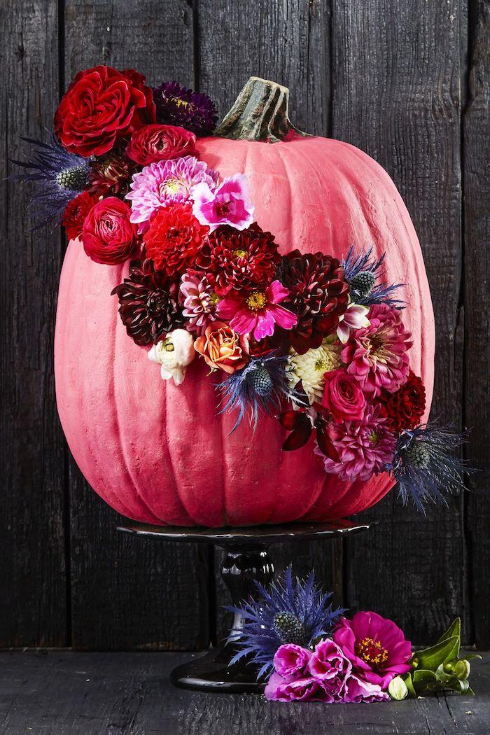 eine wand aus schwarzen holzbrettern, ein oranger großer bemalter halloween deko kürbis, rote, gelbe, blaue und violette blumen, einen halloween kürbis malen