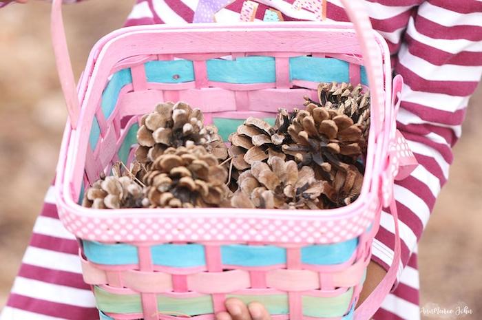 ein pinker korb aus holz und ein kleines mädchen, kleine tannenzapfen sammeln, bastelideen für kinder, ein korb mit vielen kleinen braunen tannenzapfen