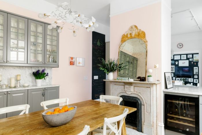eine moderne Küche mit vintage Spiegel, graue Regale, rosa mischen, langer Tisch aus Holz