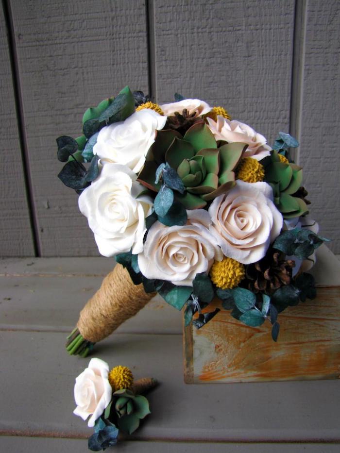 eine graue wand aus holz und ein strauß aus vielen weißen rosen und grünen und gelben pflanzen mit grünen blättern und aus kleinen braunen tannenzapfen