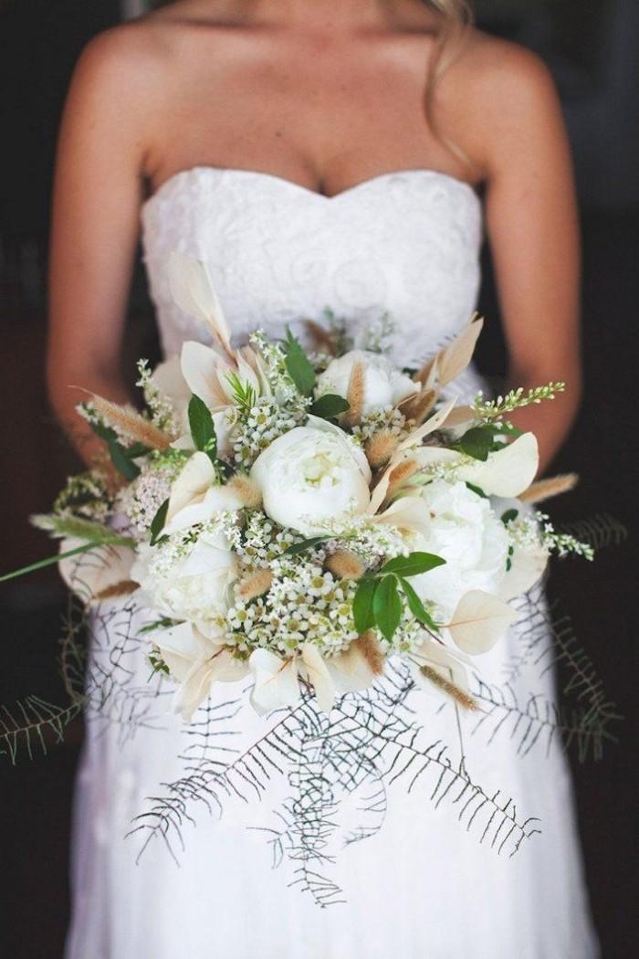 junge frau mkit einem weißen kleid und einem großen strauß moit grünen blättern und weißen blumen und weißen rosen