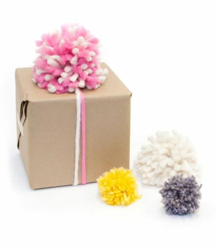 ein Geschenk in braunem Papier verpackt, Pompons basteln und als Schleife verwenden
