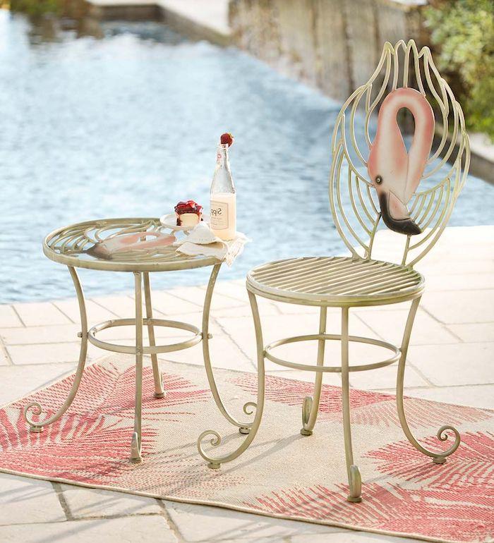 ein teppich mit pinken blättern und ein schwimmpool und ein weißer stuhl mit einer pinken deko flamingo, ein tisch mit einer flasche aus glas