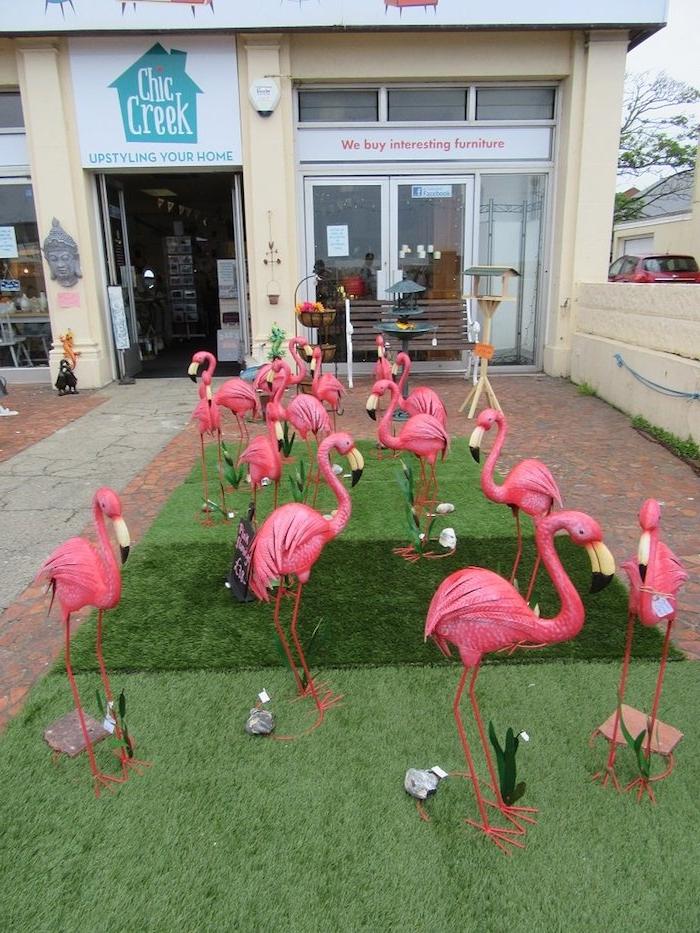 ein gelbes haus und ein grüner rasen und viele dekorative pinke flamingos und kleine graue steine, flamingo deko ideen