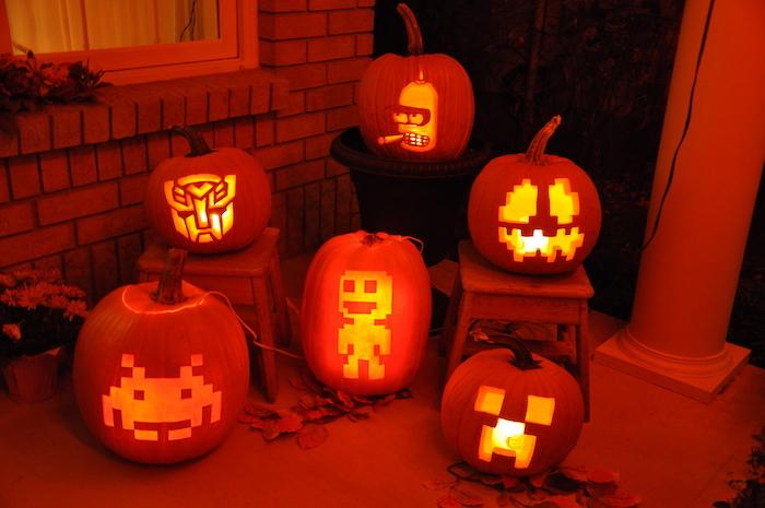 ein haus mit einem fenster und eine halloween dekoration mit sechs kleinen orangen halloween kürbissen mit gelben lustigen kürbisgesichtern, transformers und simpsons