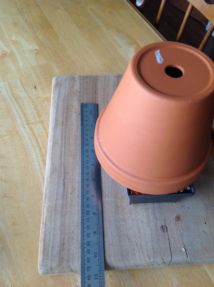 materialien für einen diy teelichtofen, ein holzbrett und ein graues lineal und ein blumentopf aus keramik, ein stuhl und ein tisch aus holz