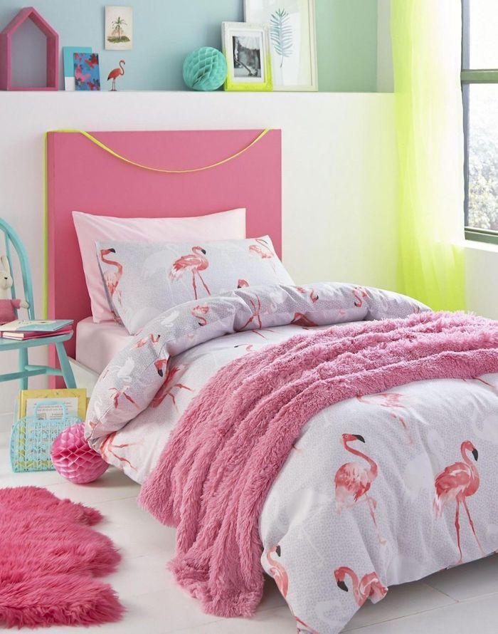 ein kinderzimmer einrichten in flamingo style, ein bett mit einer decke mit vielen kleinen pinken deko flamingos, ein fenstern und ein grüner vorhang, ein weißes kissen mit pinken flamingos und ein blauer stuhl