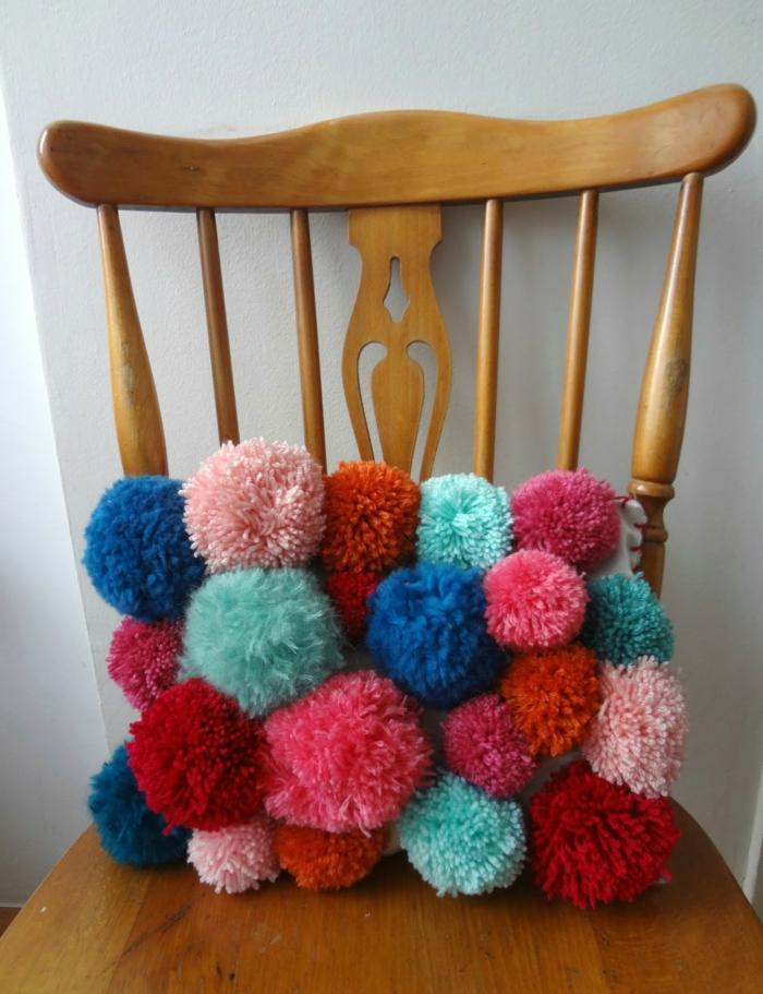 ein buntes Kissen aus Pompons in rosa und blauer Farbe, Pompon Schablone