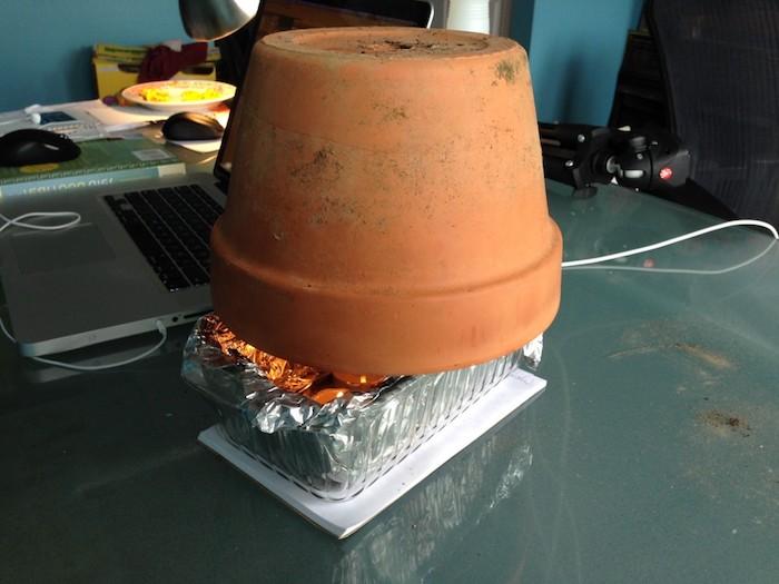 ein laptop und ein kleiner teelichtofen aus kleinen teelichtern und einem braaunen blumentopf aus keramik und mit kleinen kerzen, teelichtofen selber bauen