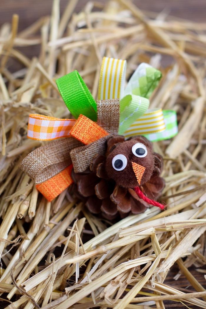 ein kleiner brauner vogel mit vielen kleinen orangen und braunen und grünen schleifen und kleinen schwarzen augen, einen vogel aus einem tannenzapfen basteln