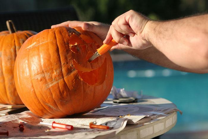 eine hand und ein tisch aus holz und ein kleiner oranger messer und zwei orange kürbisse, einen kürbis schnitzen, ein lustiges kürbisgesicht schnitzen