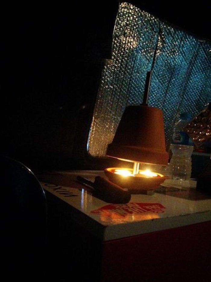 ein weißer tisch und ein schwarzer stuhl und ein kleiner teelichtofen aus einem braunen blumentopf aus keramik und mit kleinen teelichtern und weißen kerzen