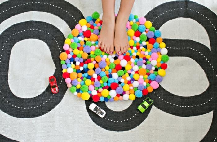 ein kleiner Teppich zum Spielen, kleine Füße von einem Mädchen, Pompon machen