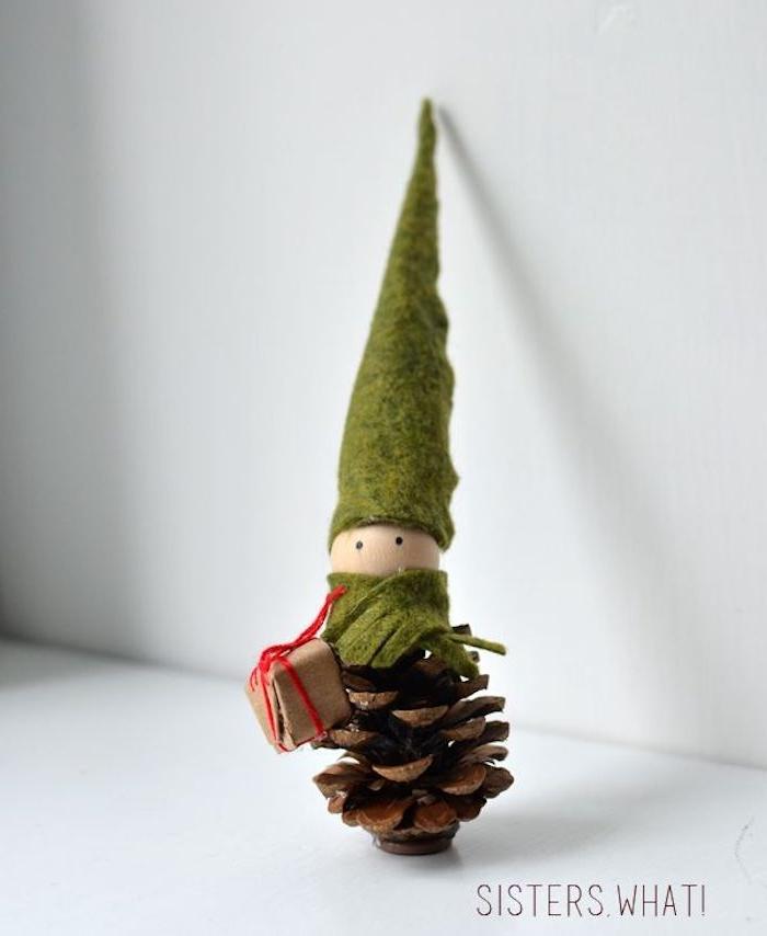 einen kleinen zwerg basteln mit einem grünen hut und mit einem braunen tannenzapfen und eine weiße wand, eine weihnachtsdeko mit tannenzapfen selber basteln