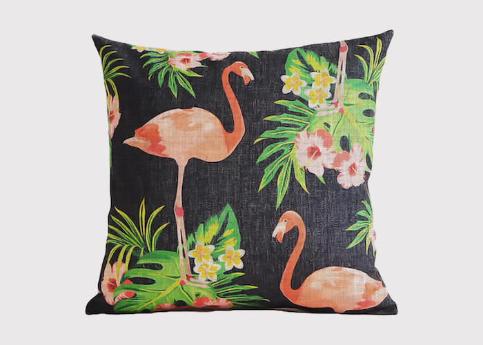 ein schwarzes kissen mit grünen pflanzen und blättern und gelben und pinken blumen und mit pinken flamingos
