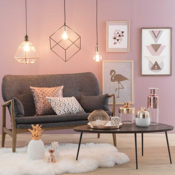 ein schwarzer, runder Tisch mit Dekorationen, ein graues Sofa, hängende Lampen, altrosa Farbe