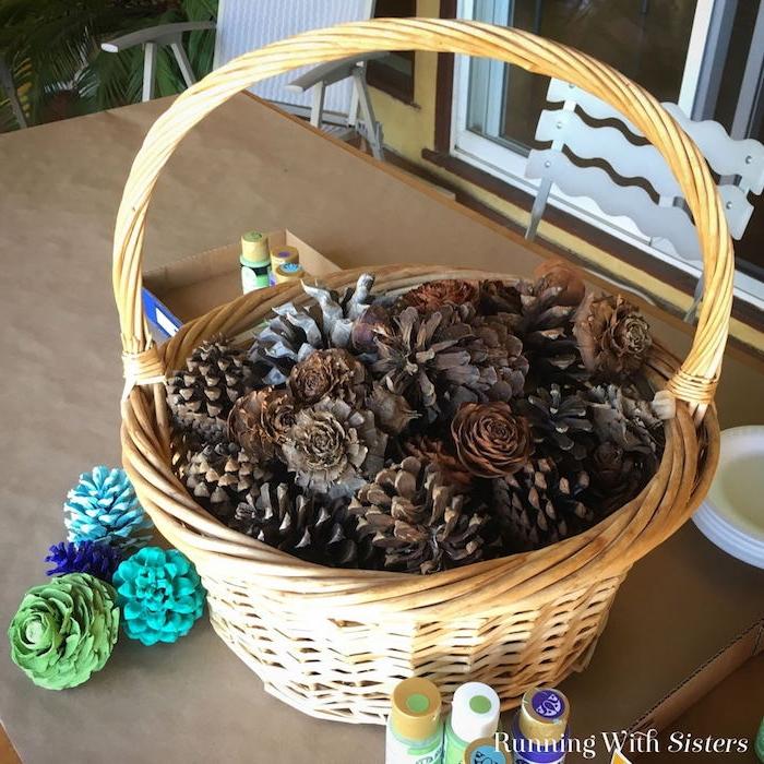 ein brauner tisch aus holz und ein brauner korb mit vielen braunen kleinen tannenzapfen, blaue, violete und grüne tannenzapfen bemalen