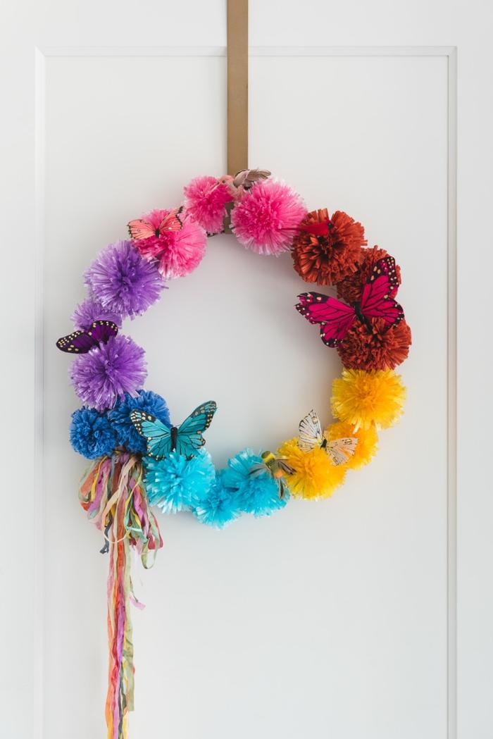 ein Kranz in vielen Farben mit kleinen Schmetterligen, an einer weißen Tür gehängt
